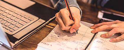 person makes note into a desk calendar